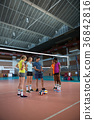 Volleyball coach discussing over clipboard with female player 36842816