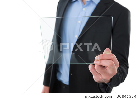 Mid section of businessman holding transparent glass interface 36845534