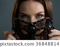 Woman wearing masquerade mask against black background 36848814