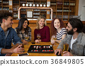 Friends interacting while having glass of beer 36849805