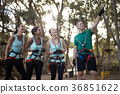 Coach assisting trainee in zip line 36851622