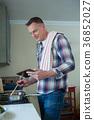 Man using digital tablet while preparing food in pan 36852027
