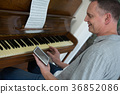 Man using digital tablet while playing piano 36852086