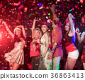 people throwing confetti and drinking. 36863413