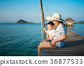 Asian mother and baby sit together on the wooded  36877533