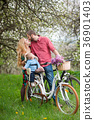 Young family on a bicycles in the spring garden 36901403