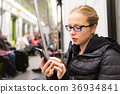 Young girl reading from mobile phone screen in 36934841