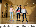 man and two woman riding on Hoverboard in mall 36936949