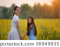 Happy Asian girl and mom walking on flower field 36949935