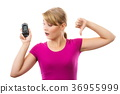 Woman holding glucometer and showing thumbs down 36955999