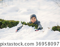A boy in winter clothes jumps into the snow. 36958097