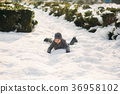 A boy in winter clothes jumps into the snow. 36958102