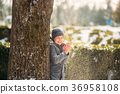 A boy warms his hands from the cold in winter 36958108