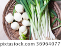 Welsh onions and onions in a big wood dish 36964077