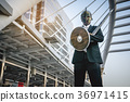 Knight businessman wearing an helm and steel sword 36971415
