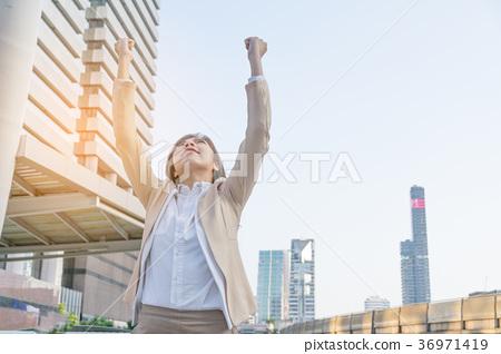 Winner woman celebrating success on city 36971419