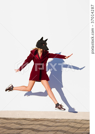 Happy girl in dog head mask jumping  37014287