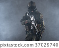 Serious soldier holding assault rifle in hands 37029740