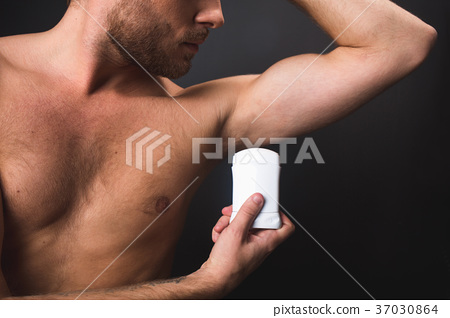 Unshaven man with nude torso holding deodorant 37030864