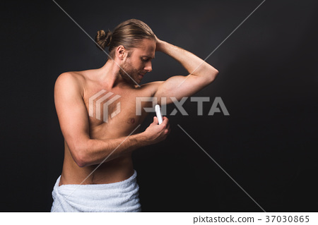 Unclothed male in loop towel with deodorant 37030865