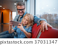 Mature man and small girl are using mobile phone 37031347