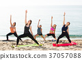 Young concentrated women exercising yoga poses on sunny beach 37057088