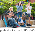 Portrait of four teenagers playing music together outdoors 37058045