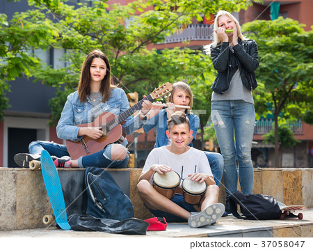Portrait of four teenagers playing music together outdoors 37058047