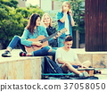 Teenagers playing music outdoors . 37058050