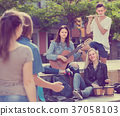 Adult girls and boys with musical instruments 37058103