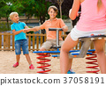 kids are teetering on the swing on the playground. 37058191