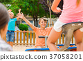 Cheerful children are teetering on the swing 37058201