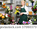 Florist in apron holding scissors and fixing flowers 37060373