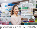 Portrait of smiling beautiful girl choosing bird cage 37060497