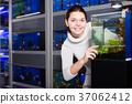 Teenage girl shows an aquarium with fish fry 37062412
