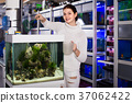 Girl with net and watering can is going catch young small fish from aquarium in aquarium shop 37062422