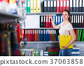 Portrait of positive woman looking products in store 37063858