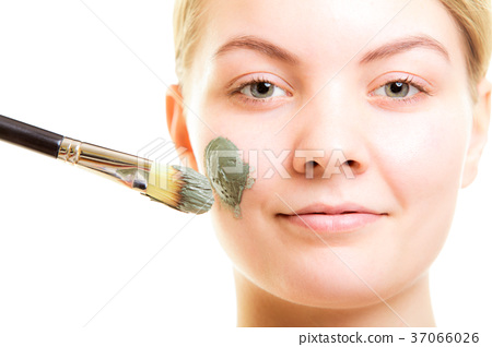 Skin care. Woman applying clay mud mask on face. 37066026