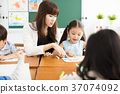 children drawing in the classroom and teacher  37074092