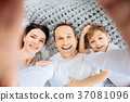 Happy man taking a selfie of his family on bed 37081096