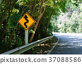 Yellow sign with curved arrow and road 37088586