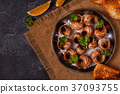Fried snails with lemon, baguette and parsley. 37093755