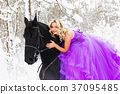 Young woman in long dress riding a horse in winter 37095485