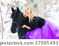 Young woman in long dress riding a horse in winter 37095493