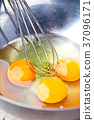 whisking eggs in metal bowl 37096171