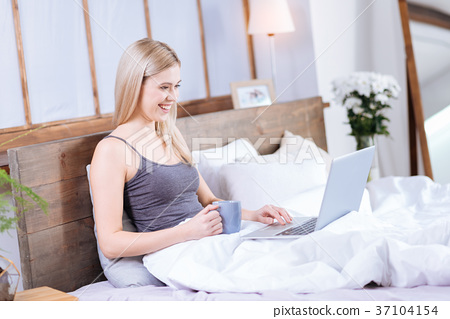 Beautiful woman using laptop and drinking coffee 37104154