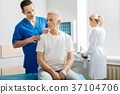 Handsome nice man touching his patients shoulder 37104706