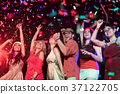 People throwing confetti and drinking at party. 37122705