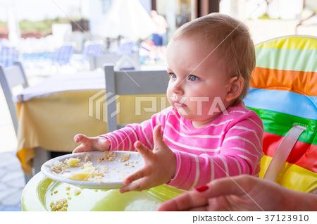 Little baby girl eating lunch on the high chair 37123910