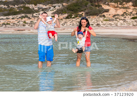 Family with little twins having fun in the water 37123920